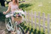 Fotografie partial view of woman in stylish dress with retro bicycle with wicker basket full of flowers at countryside