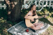 Fotografie attractive young woman playing acoustic guitar while resting on blanket under tree at countryside