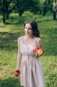 portrét usměvavá mladá žena v šatech s zralá jablka na venkově