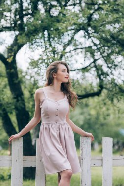 pensive beautiful woman in stylish dress standing at white fence at countryside