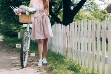 partial view of woman in dress with retro bicycle with wicker basket full of flowers at countryside