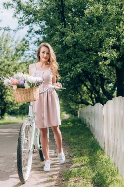 young beautiful woman in dress with retro bicycle with wicker basket full of flowers at countryside