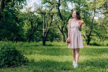 smiling young woman in dress with ripe apples walking at countryside