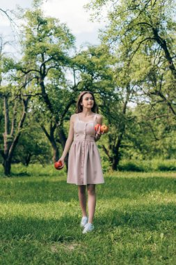 young woman in dress with ripe apples walking at countryside