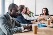 selective focus of multicultural business people having business meeting in office