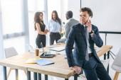 Selektivní fokus kavkazské podnikatel mluví na smartphone a mnohonárodnostní kolegy za v úřadu