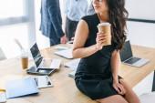 Fotografie částečný pohled africká americká podnikatelka s kávou jít a za kolegy v kanceláři