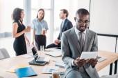 Selektivní fokus usměvavý americký podnikatel pomocí tabletu a kolegy na pracovišti v úřadu