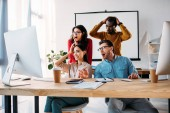 Fotografie shocked multiracial business team working on project together in office