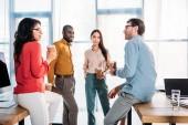 Fotografie interracial business colleagues having conversation during coffee break in office
