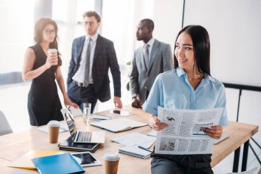 selective focus of asian businesswoman with newspaper and colleagues behind in office
