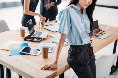 partial view of businesswoman using smartphone and colleagues behind in office