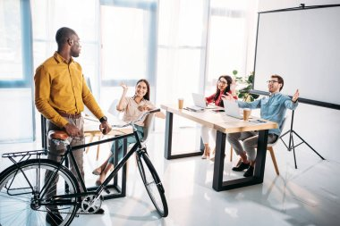 multicultural business people greeting african american colleague with bicycle in office