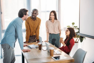 interracial group of business colleagues discussing work during coffee break at workplace in office