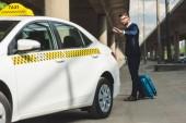 Fotografie elegantní mladý muž s smartphone a kufr na taxík