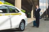pohledný mladý muž v obleku a brýle mluví o smartphone stoje s kufrem v blízkosti taxi
