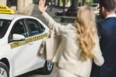 Selektivní fokus mladá žena mává rukou a šla s mužem na taxi