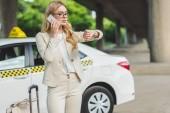 mladá žena mluví o smartphone a kontrola Náramkové hodinky vstoje se zavazadly u taxíku