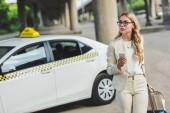 mladá žena v brýlích držení smartphone a koukal když stál poblíž taxi taxi na ulici
