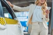 oříznuté záběr usměvavá blondýnka pomocí smartphone stoje u taxíku