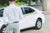 zadní pohled na mladého muže řidič chystá taxi taxi na ulici