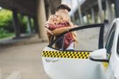 krásná mladá dvojice objímání poblíž taxi cab