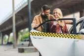 šťastný elegantní mladý pár otevírací dveře taxíku dohromady