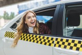 s úsměvem mladá žena koukal oknem taxíku