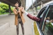 Fotografie dívka v taxi a muž na ulici dávat prsty si navzájem