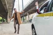 dívka sedící v taxíku a mává rukou, zatímco mladý muž běží a při pohledu na auto