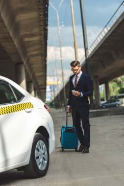 handsome young man using smartphone while standing with suitcase near taxi