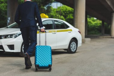 back view of young man with suitcase running to taxi cab