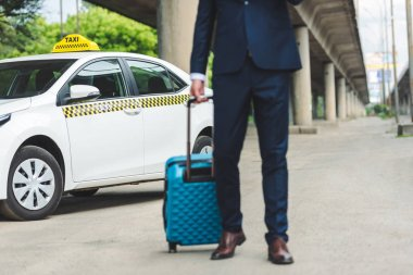 cropped shot of man in suit holding suitcase while standing near taxi cab