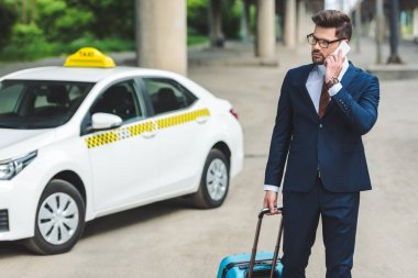 handsome man talking by smartphone while standing with suitcase in taxi cab