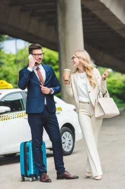 smiling blonde girl holding paper cup and looking at handsome man talking by smartphone while standing with suitcase near taxi