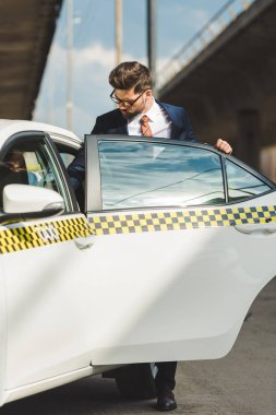 handsome young man in fashionable suit and eyeglasses opening door of taxi cab