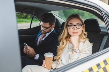 young woman holding paper cup and looking away while man using smartphone in taxi