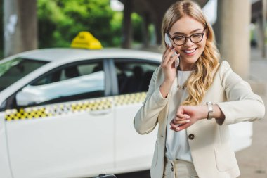 smiling blonde woman in eyeglasses talking by smartphone and checking wristwatch while standing near taxi cab