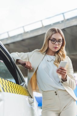 beautiful blonde woman in eyeglasses leaning at taxi cab and using smartphone