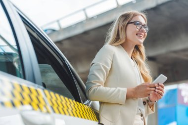 low angle view of smiling blonde girl in eyeglasses holding smartphone and looking away while standing near taxi
