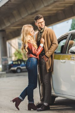 happy stylish young couple standing together near taxi cab