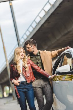 beautiful stylish young couple standing together near taxi cab