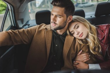 young man looking at car window while girlfriend sleeping on his shoulder in taxi