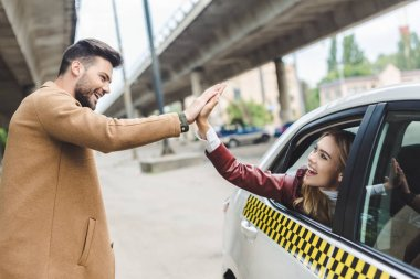 happy young couple giving high five each other, girl sitting in cab and man standing on street