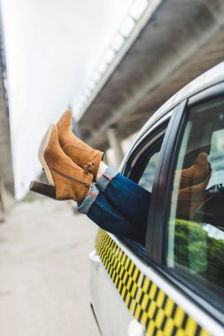 cropped shot of female legs in stylish shoes in open window of taxi
