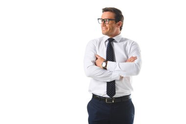 smiling businessman in eyeglasses standing with crossed hands isolated on white background