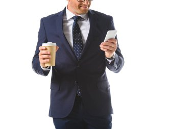 Cropped image of businessman checking smartphone and holding paper cup of coffee isolated on white background stock vector