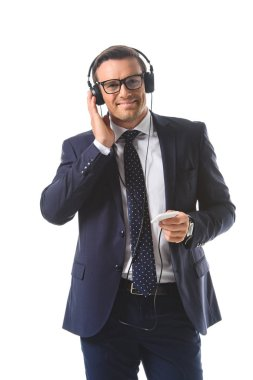 smiling businessman in eyeglasses listening music in headphones with smartphone isolated on white background
