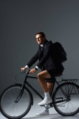 Fotografie stylish man with backpack sitting on bicycle on grey background