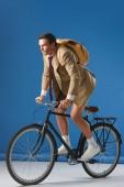 Fotografie cílené muž s batohem jízda kole a koukal na modré